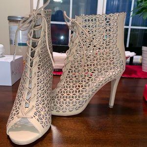 Open toed cream stiletto heeled boots.